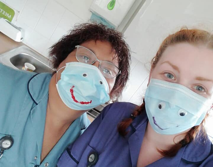 Two carers pose with smiley faces drawn on their face masks