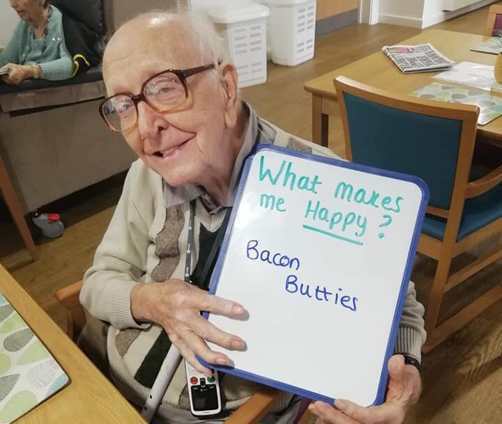 Resident holding a sign showing what makes them happy